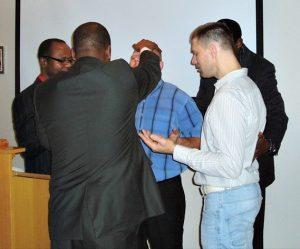 Pastor Matthew, biskop Bigirimana og pastor Jack går i forbønn for de nydøpte latvierne Maris og Sandis - Hope Christian Fellowship Church_picmonkeyed