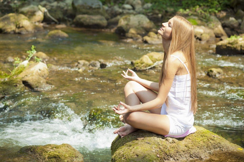 Kvinne mediterer ved elv